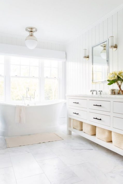a light-filled neutral bathroom with a shiplap wall, a large vanity and a free-standing tub