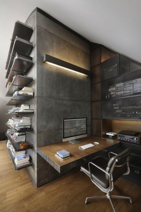 a minimalist industrial home office with concrete walls, a plywood wall mounted desk, a leather chair and some metal shelves