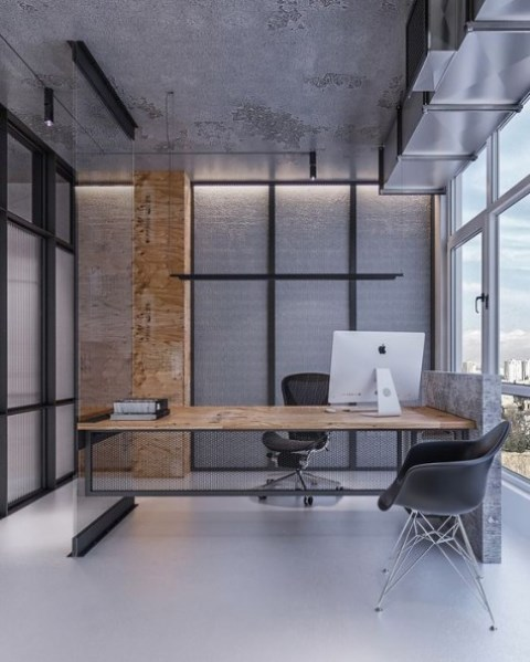 a minimalist meets industrial home office with much concrete and metal in decor, a catchy desk and a glazed wall