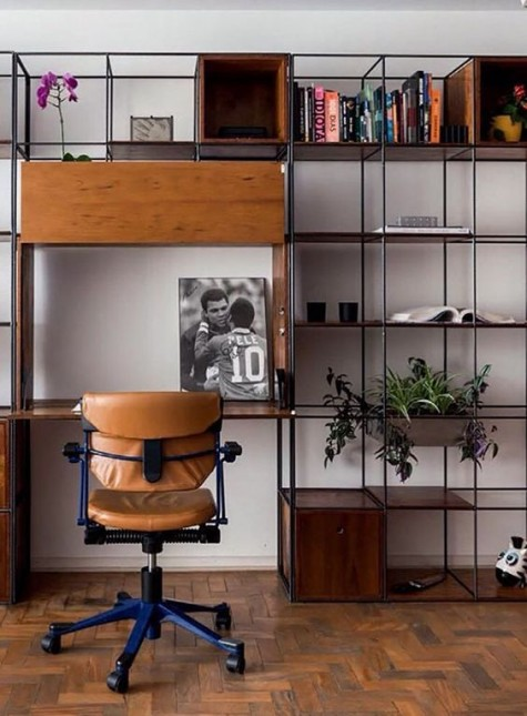 a modern meets industrial home office with a large shelving and storage unit that includes a desk space and a leather chair