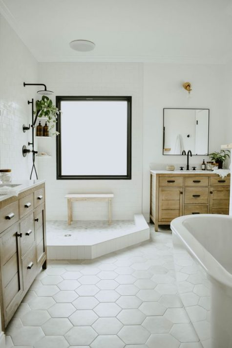 a modern neutral bathroom with hex and subway tiles, wooden vanities and touches of black for drama