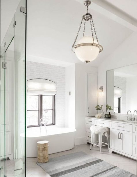 a neutral bathroom with a modern tub, a catchy pendant lamp, a striped rug and a chic vintage vanity with drawers
