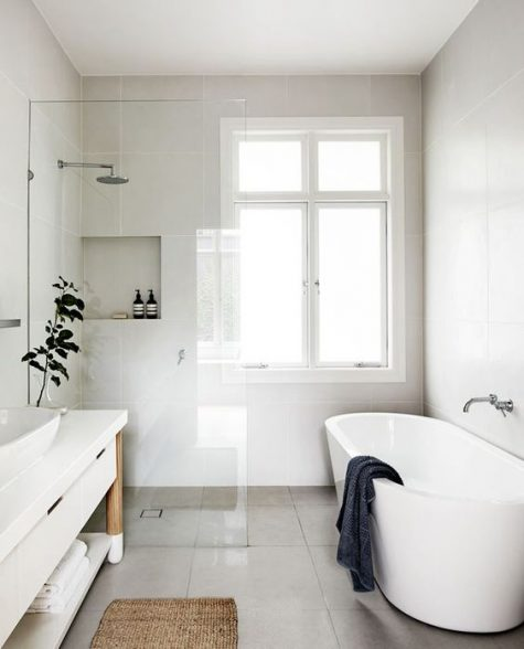 a neutral contemporary bathroom clad with large scale tiles, with a shower space and a tub and a large sleek vanity