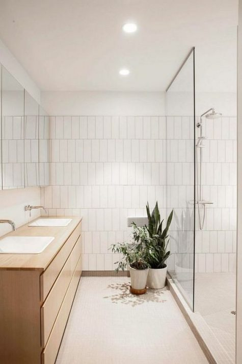 a neutral contemporary bathroom with tiles, a shower space and a double wooden vanity plus potted greenery