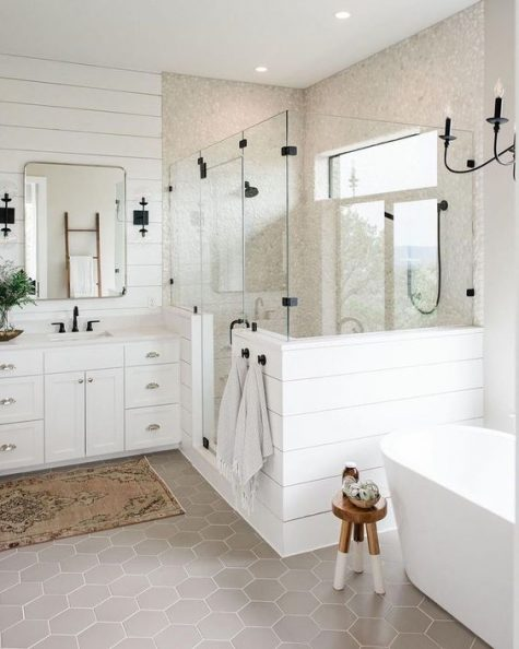 a neutral farmhouse bathroom clad with shiplap, a wooden vanity, a free-standing tub and touches of black