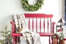 a red bench, evergreens and berries, candle lanterns and a greenery wreath on the wall for a Christmas feel