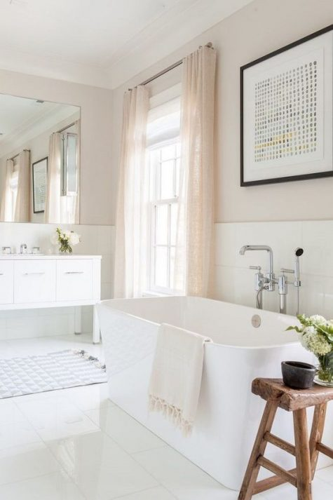 a refined neutral bathroom with a white tub, vanity and tiles, a wooden bench and blush curtains