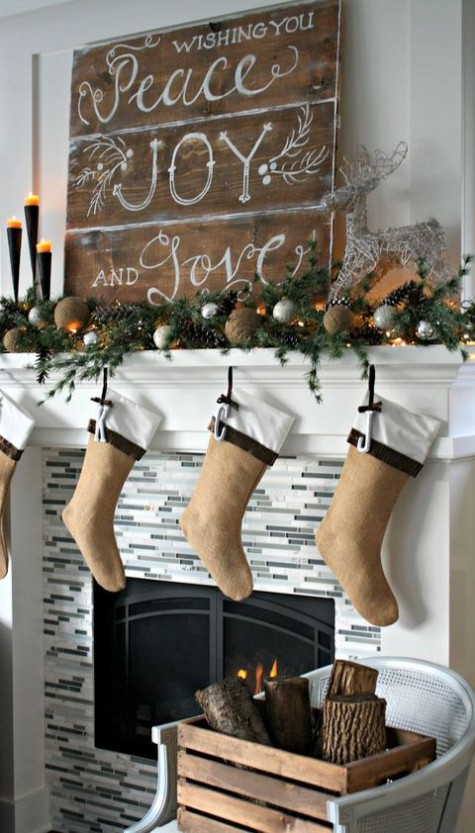 a rustic Christms mantel with a large sign, an evergreen and pinecone garland, lights, burlap balls and burlap stockings
