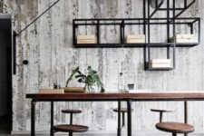 a rustic industrial home office with a large wooden desk and stools attached, exposed piping and a shelving unit