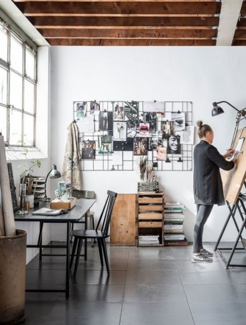 a rustic industrial home office with wooden and metal furniture, a wire grid for notes, vintage metal lamps