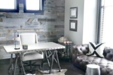 a rustic meets industrial home office with a weathered wooden wall, a metal trestle desk, a leather sofa and a metal stool