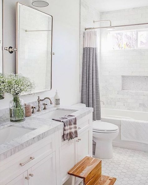 a serene neutral bathroom with hex and marble tiles, a marble vanity countertop, some blooms and a printed curtain