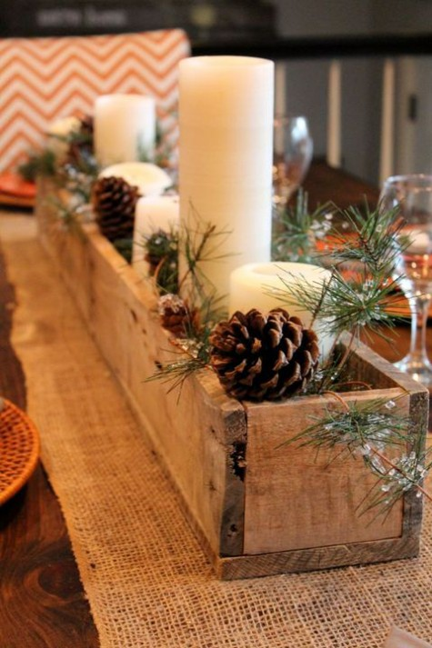 a simple rustic Christmas centerpiece of a wooden box with pinecones, evergreens and pillar candles
