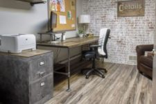 a simple rustic industrial home office with a desk that changes height, leather chairs, a metal cabinet