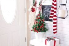 a small and bright Christmas entryway with evergreens, white and red ornaments, a small tree, a scarf and stockings