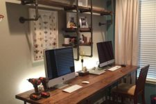 a small industrial shared home office with a large shelving unit with pipes, a mathcing desk and wooden chairs