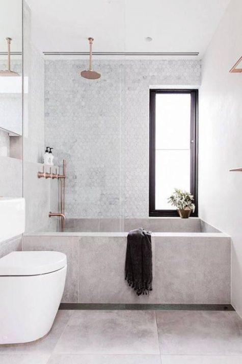 a small neutral bathroom with a tile clad tub, copper fixtures and a hex tile wall for a chic look