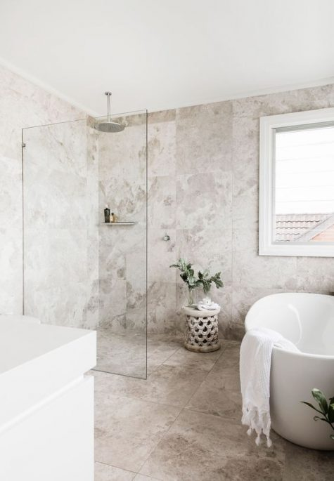 a stylish contemporary bathroom with catchy neutral tiles, a free-standing tub nand a carved wooden table