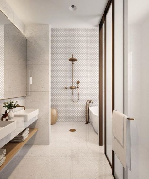 a stylish minimalist bathroom with penny and oversized white tiles, aged metal touches and a mirror wall