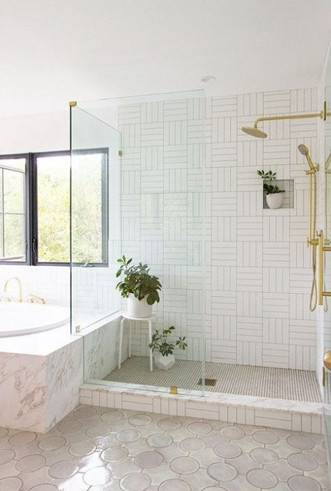 a stylish neutral bathroom with a geometric tile shower space, a stone clad bathtub, greenery in pots and touches of gold