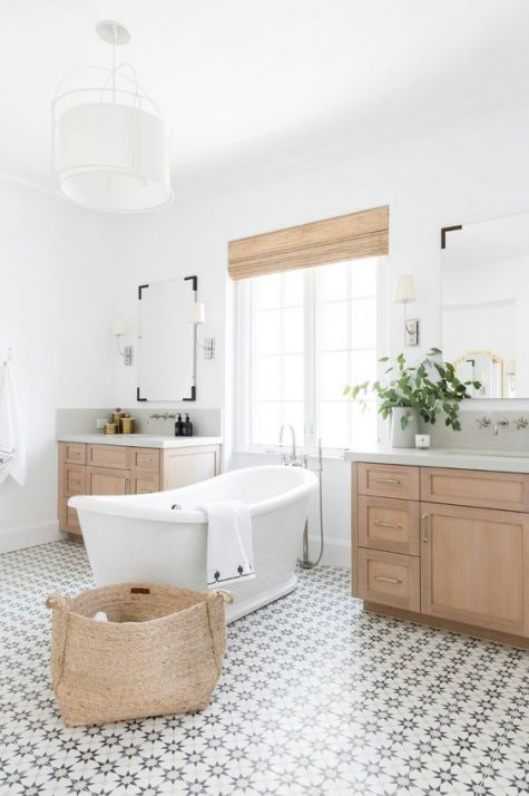 a stylish neutral bathroom with a star tile floor, wooden vanities, wooden shades and a basket for storage