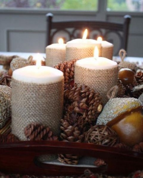 a tray with pinecones, vine balls, glitter acorns and candles wrapped with burlap make up a nice rustic centerpiece