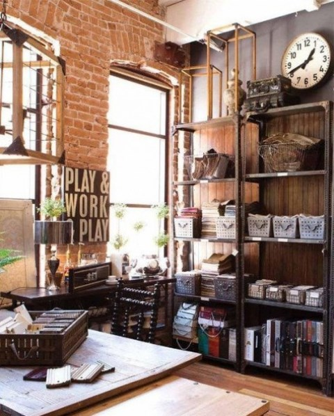 a vintage industrial home office with metal shelving units, a wooden desk and chair, some lamps and a vintage clock