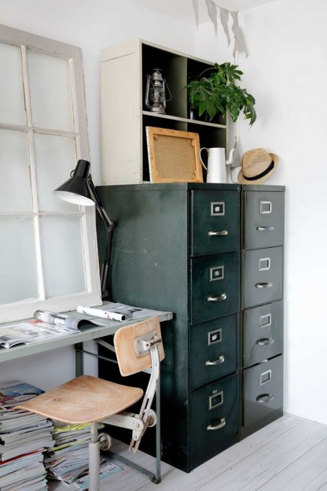 a vintage industrial home offie, a metal desk, a metal and wood chair, a metal paper cabinet and some greenery