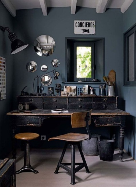 a vintage meets industrial home office with a large vintage wooden desk, metal and wood chairs, vintage lamps and mirrors