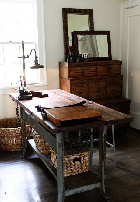 a vintage meets industrial home office with a wooden cabinet, mirrors, a vintage metal desk and baskets for storage