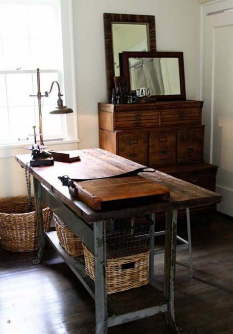 a vintage meets rustic home office with a large metal and wood desk with baskets, a large wooden dresser with mirrors and a metal stool