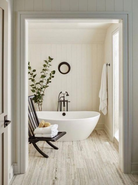 a warm-colored bathroom clad with shiplap, with some dark touches and a free-standing tub