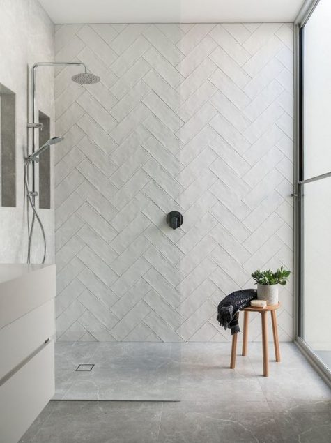 a welcoming neutral bathroom with long white tiles, stone tiles on the floor and a white vanity