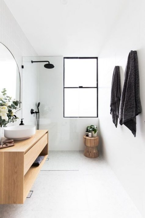 a white minimalist bathroom with a seamless shower space, a wooden vanity and stool and touches of black for drama