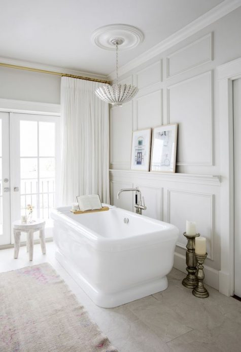 an elegant neutral bathroom with paneled walls, a pendant lamp, some white furniture and curtains