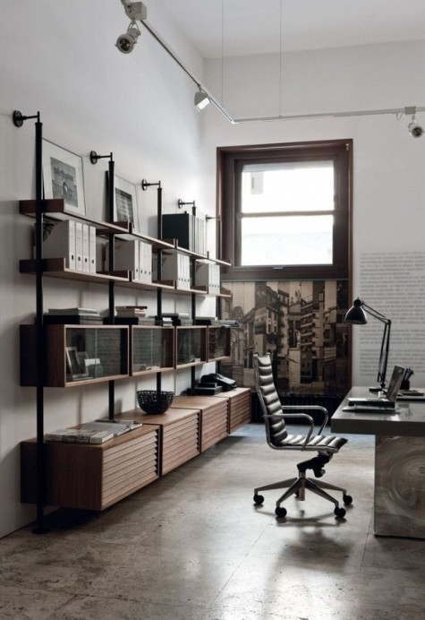 an industrial home office with a stone and wood desk, a large shelving unit or metal and wood and some vintage metal lamps