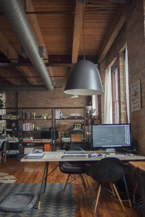 an industrial home office with a wooden ceiling, exposed pipes, a minimalist desk and chairs plus metal shelving units