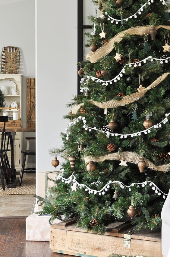 neutral rustic Christmas tree decor with pinecones, burlap ribbons, pompom garlands and aged metal ornaments