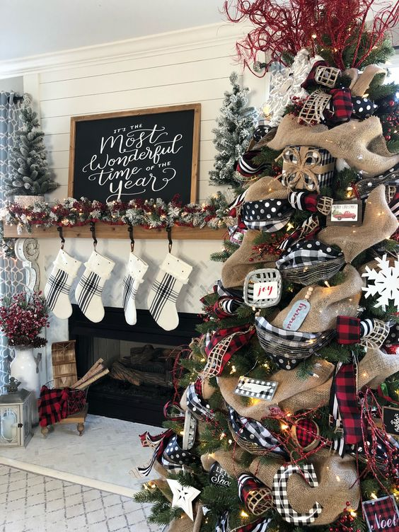 rustic Christmas decor with buffalo check, burlap, lights, touches of plaid, snowy evergreens and plaid stockings