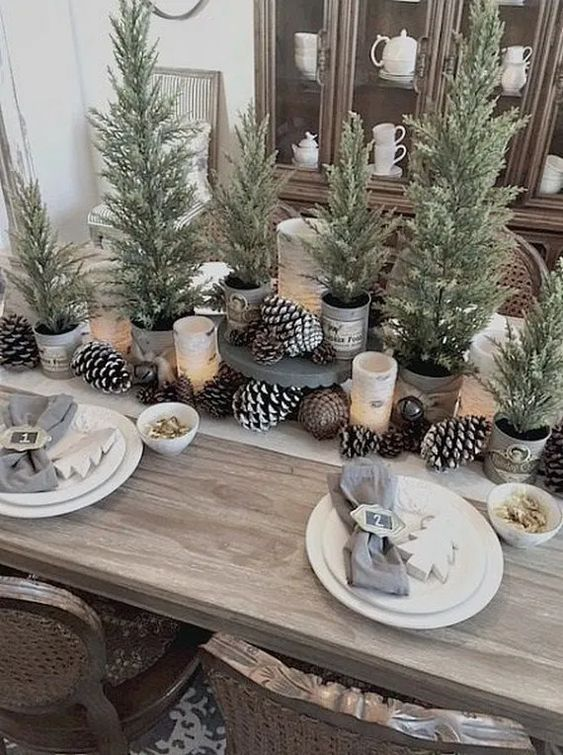 rustic Christmas table styling with pinecones, candles and lots of mini trees in pots but with no decor