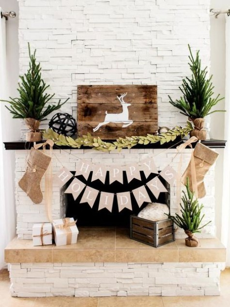 rustic fireplace styling with burlap stockings, mini Christmas trees, a greenery garland, a deer sign and a crate