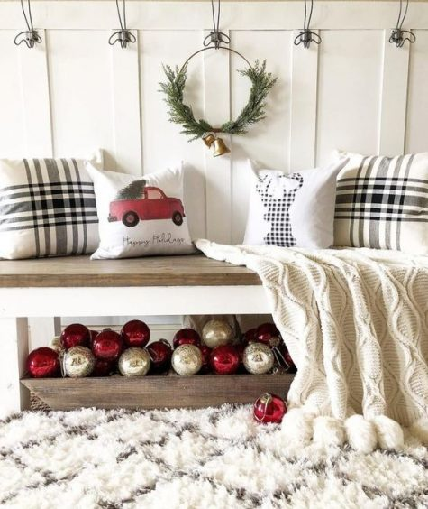 simple and cute Christmas entryway decor with a wooden box of ornaments, an evergreen wreath and some pillows