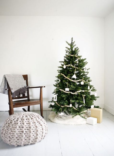 a Christmas tree decorated with wooden beads, white ornaments and a faux fur skirt in white looks al-natural