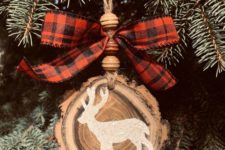 02 a beautiful rustic Christmas ornament made of a wood slice with a live edge, wooden beads and a plaid bow