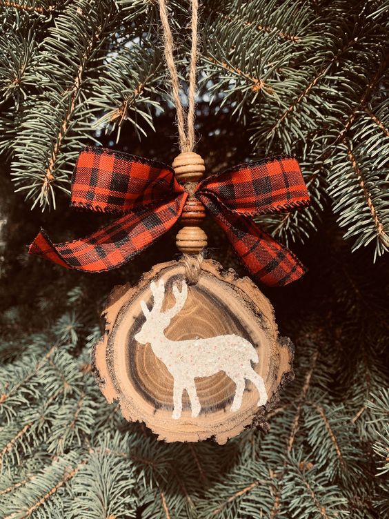 a beautiful rustic Christmas ornament made of a wood slice with a live edge, wooden beads and a plaid bow