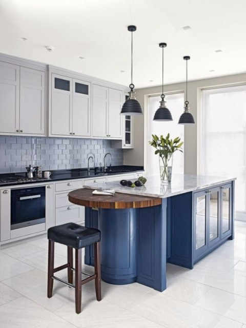 a blue kitchen island with white cabinets and different countertops - black for cabinets and a white stone one for the island