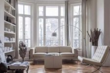 02 a contemporary Parisian living room with all-whites and a hardwood parquet floor to soften the space