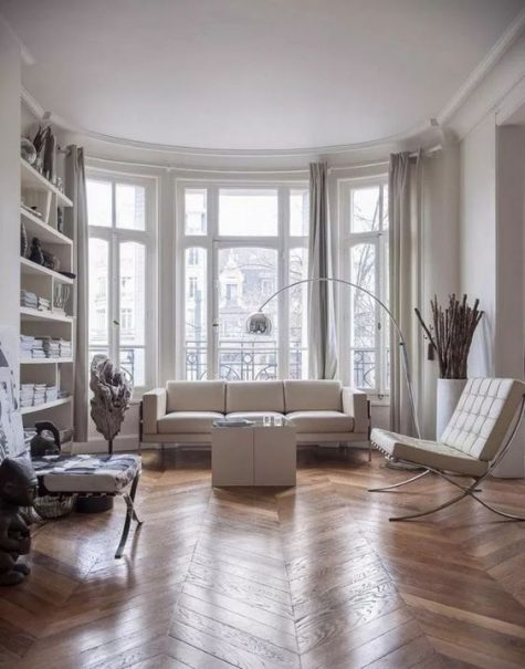 a contemporary Parisian living room with all whites and a hardwood parquet floor to soften the space