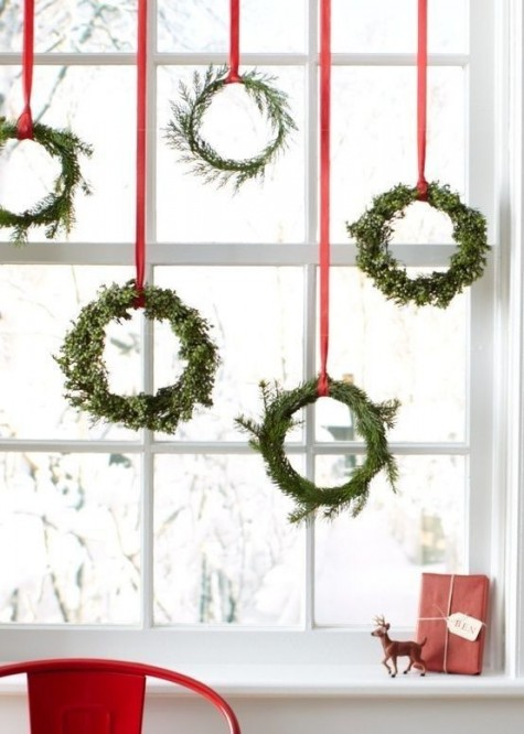 evergreen wreaths with red ribbons to decorate the window is a cool holiday look, a fresh take on traditional decor