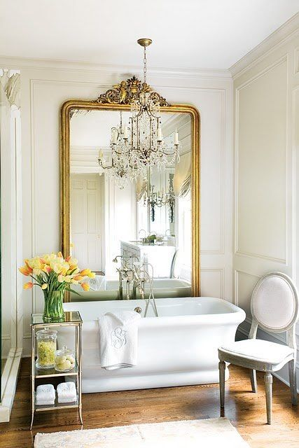 a chic Parisian bathroom with a crystal chandelier, a statement mirror in a gilded frame, a chic tub and vintage furniture
